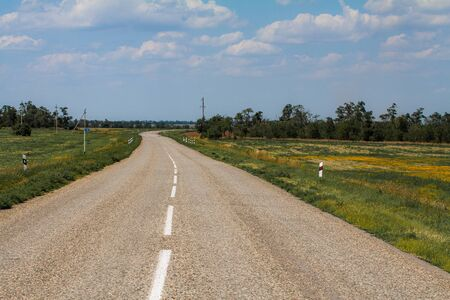Smooth asphalt road to the mountains road to the distance beyond the horizon to the clouds. Stok Fotoğraf