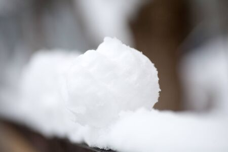 real snowballs with their hands clasped from the fresh snow in winter on the street