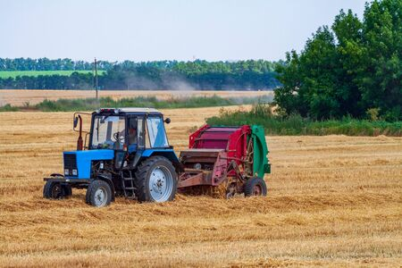 A tractor with a trailed bale making machine collects straw rolls in the field and makes round large bales Stockfoto