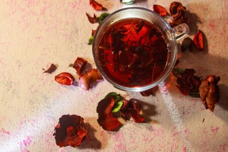 Red Hot Hibiscus tea in a glass mug on a wooden table among rose petals and dry tea custard with carcade