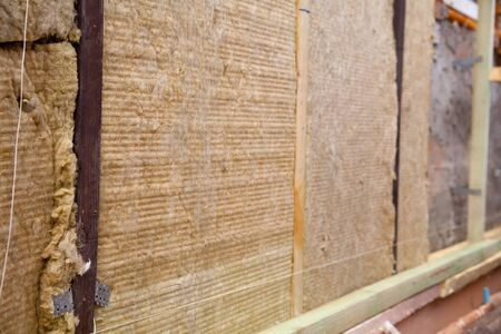 warming the walls of a stone house with a stone wool heater. Ecological insulation of rooms with building a house. Installation of cellulose thermal insulation in the wall of the frame house