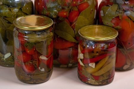 Canned bitter red pepper peeled in a glass jar in a home garden by a farmer
