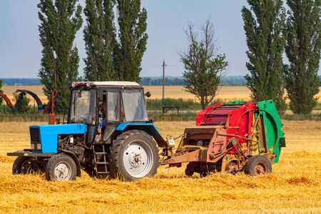 A tractor with a trailed bale making machine collects straw rolls in the field and makes round large bales 写真素材