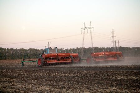 Agricultural mechanical seeders of grain crops. Tactor with a seeder sows grain in the field. A farmer on a tractor with a seeder processes the field.