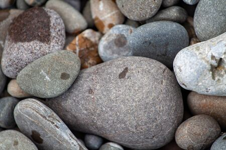 sea pebbles colored granite on the beach background stones. The shore of the beach with sand and pebbles washed by the waves of the sea.