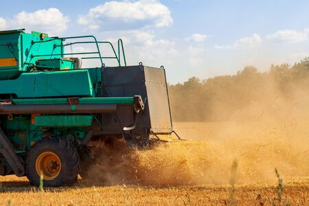 A harvester in a field mows ripe dry wheat emitting clouds of dust. A farmer cultivates his farmland. Harvest.