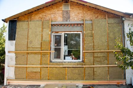 warming the walls of a stone house with a stone wool heater. Ecological insulation of rooms with building a house. Installation of cellulose thermal insulation in the wall of the frame house Stock Photo