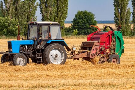 A tractor with a trailed bale making machine collects straw rolls in the field and makes round large bales Reklamní fotografie