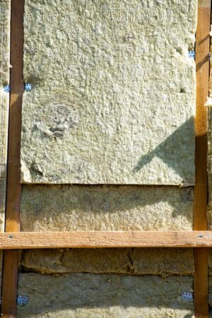 warming the walls of a stone house with a stone wool heater. Ecological insulation of rooms with building a house. Installation of cellulose thermal insulation in the wall of the frame house 版權商用圖片
