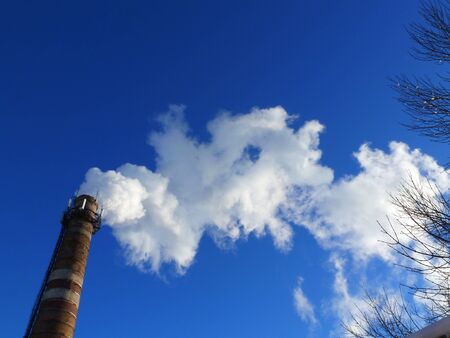 Pipes of an old factory throw clouds of poisonous white smoke into the sky polluting the atmosphere. Urban smog from smoke from boiler houses. White smoke from a chimney against a blue clear sky.