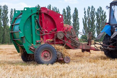 A tractor with a trailed bale making machine collects straw rolls in the field and makes round large bales Фото со стока