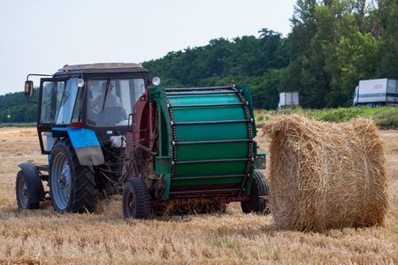 A tractor with a trailed bale making machine collects straw rolls in the field and makes round large bales 版權商用圖片