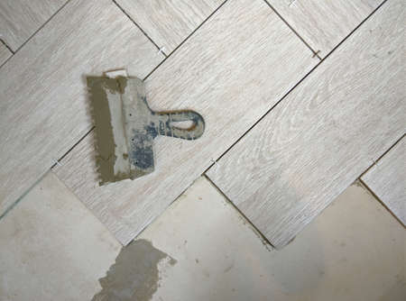placing a porcelain stoneware floor with Bricklayer special tools, plastic tongs and blue adjustment wedges. Imagens - 159702189