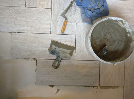 placing a porcelain stoneware floor with Bricklayer special tools, plastic tongs and blue adjustment wedges. Imagens - 159702190