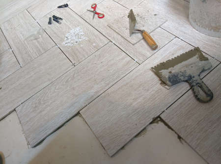 placing a porcelain stoneware floor with Bricklayer special tools, plastic tongs and blue adjustment wedges.