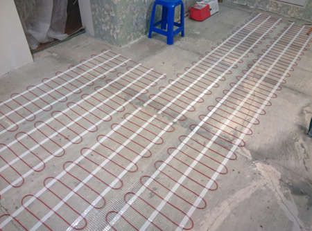 Closeup of concrete and red electrical wires. Electric floor heating system installation in new house. Closeup of concrete and red electrical wires