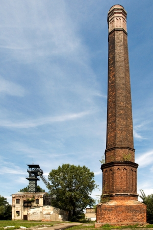 tall chimney: Old coal mine shaft with a mining tower in the foreground tall chimney