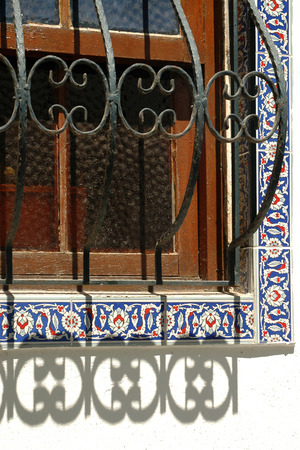 Decorative window grilles with paneling around the window photo