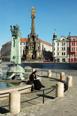 OLOMOUC, CZECH REPUBLIC CIRCA MAY 2005 - Unknown nun sitting on the edge of the Arion fountain, in the Holy Trinity  plague  Column With Chapel
