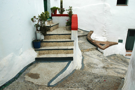 Stairs to entry door in a narrow alley in Spanish Andalusia photo