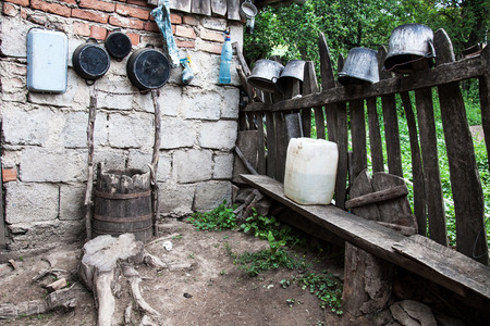 Pots and junk in the nook of the yard of one Romanian village photo