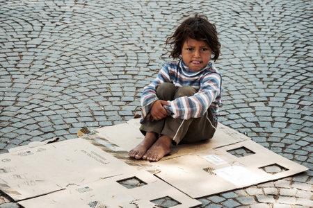 ティラナ、アルバニア、ティラナの通りに古いボックスに座っている未知のホームレスの子供 2010 年 5 月 14 日-
