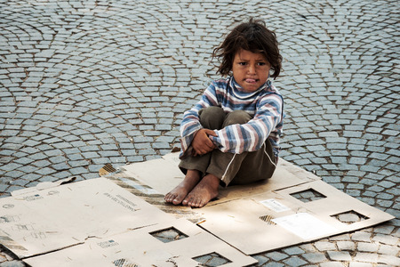 poverty: TIRANA, ALBANIA, MAY 14, 2010 - Unknown homeless kid sitting on the old box on the street in Tirana