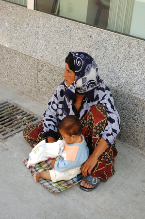 pauper: KUSADASI, TURKEY, JUNE 16, 2005 - Woman beggar with her child  asking for money Editorial