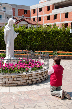 sacraments: MEDJUGORJE, BOSNIA AND HERZEGOVINA, MAY 12, 2010 - Woman pilgrim ahead of Madonna of Medjugorje Editorial