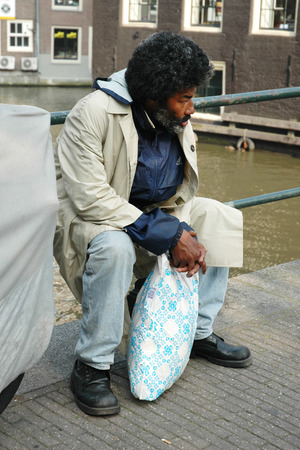 mendicant: AMSTERDAM, HOLLAND, SEPTEMBER 03, 2005 - Darky homeless man sitting at canal in Amsterdam