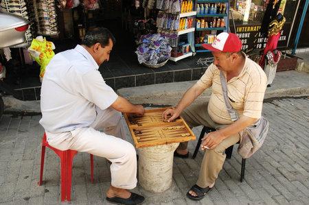 KUSADASI, TURKEY, JUNE 16, 2005 - Two men play their favorite game on the street Editorial