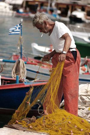 PYTHAGOREIO, GREEK, JUNE 10, 2005 - Old fisherman preparing fishing net Редакционное
