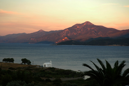 A small white church on the Aegean coast at sunset on the Greek island of Samos, in the background of the Turkish mountains photo