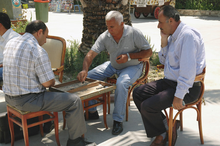 KUSADASI, TURKEY, JUNE 16, 2005 - Two men play their favorite game on the street in the shade of palm trees Editorial