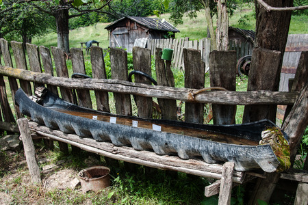 Primitive drinking trough for farm animals made from old tire in Romania