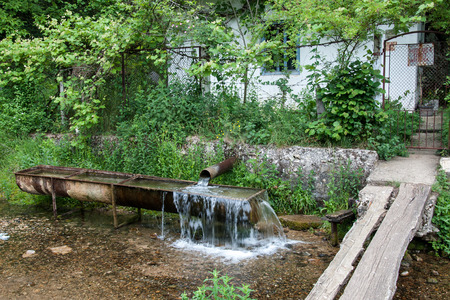 poorness: Old water trough as a source of water in rural setting before the front entrance to house Stock Photo