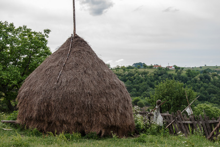 Old traditional haystack in the yard of Romanian farm photo