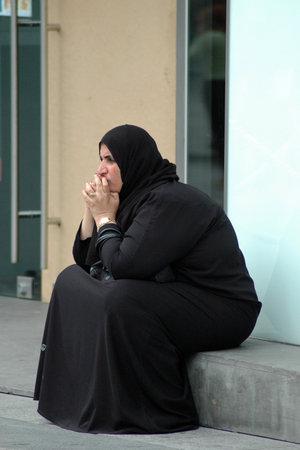 femme musulmane: PARIS FRANCE 19 ao�t 2006 Jeune femme musulmane assis en face de la boutique dans une rue de Paris