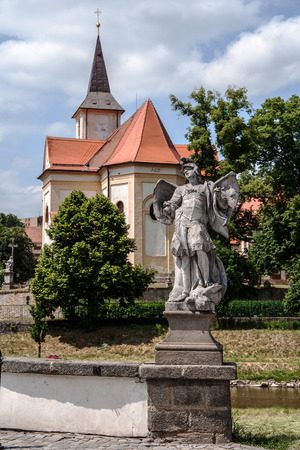 enduring: Baroque statue of Archangel Michael at the edge bridge in Enduring Freedom, in the background the church of St. John the Baptist, Czech Republic Stock Photo