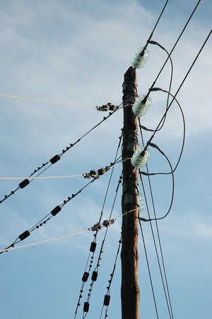 insulators: Old wooden column with electric wires and cables on glass insulators