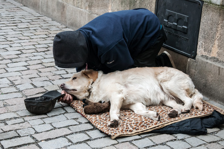 destitute: PRAGUE, CZECH REPUBLIC - FEBRUARY 13, 2016: Kneeling man and his dog begging on the Charles Bridge
