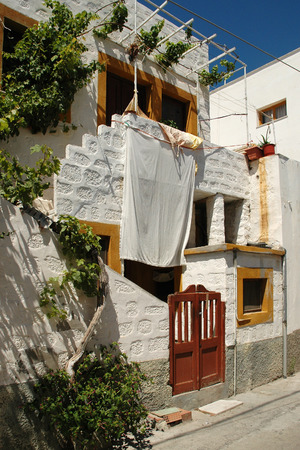 Unusual entrance to the house with vines on the Greek island of Samos