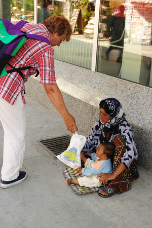 destitute: Kusadasi, TURKEY - JUNE 16, 2005: Woman Gives to the beggar woman food for baby Games Editorial