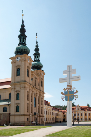 VELEHRAD, CZECH REPUBLIC - JUN 01, 2019: Papal coat of arms on the cross before the Basilica of the Assumption of Virgin Mary and St. Mary. Cyril and Methodius in Velehrad, which is the most important pilgrimage church in Czech Republic Редакционное