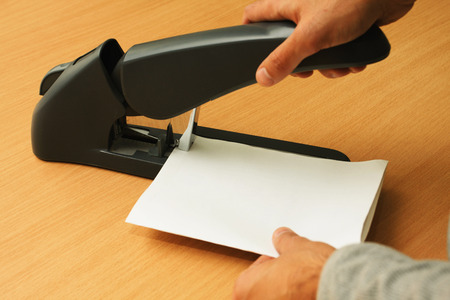 upholster: binding papers with stapler by both hands