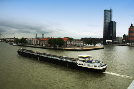 uptown: City of Rotterdam uptown skyline by the river in South Holland with large boat, the Netherlands. Stock Photo