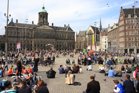 dam square: Amsterdam, The Netherlands - Avgust 17, 2015: The Dam square in the center of Amsterdam with sitting and relaxing people on a sunny weekend day.