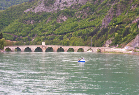 former yugoslavia: Famous bridge on the Drina in Visegrad, Bosnia and Herzegovina, with large hill