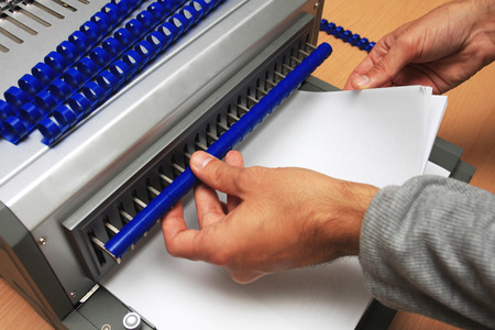 Gray Binding machine with man who works on it Stockfoto