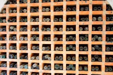 dusty: Dusty old wine bottles stacked in the wine cellar